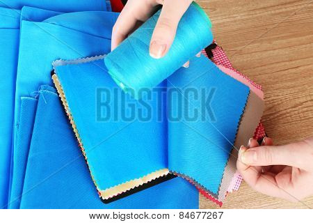 Colorful fabric samples with thread in female hands on wooden table background