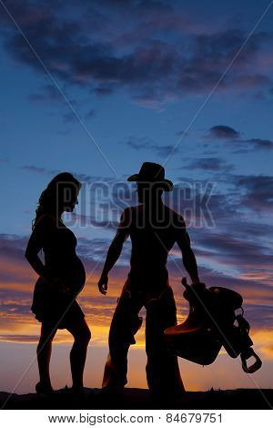 Silhouette Of A Pregnant Woman And A Cowboy With A Saddle