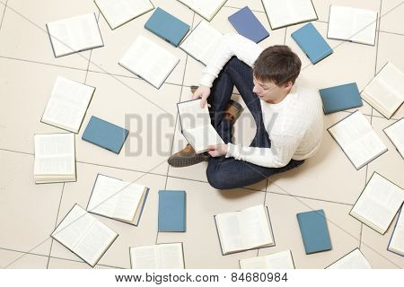 Man reading a book, top view. Blurred text is unreadable