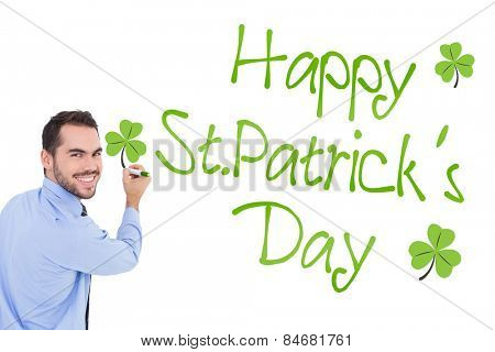 Happy businessman in shirt writing with marker against shamrock