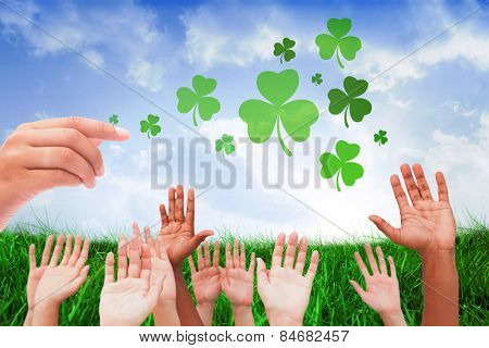 Hands raising in the air against field of grass under blue sky