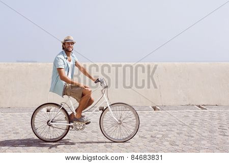 Handsome man on a bike ride on the pier on a sunny day
