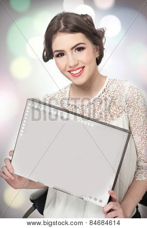 Hairstyle and make up - beautiful young girl holding a white paper in her hands. Genuine natural