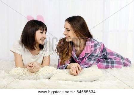 Two girls in pajamas lying on fluffy white carpet, on light background