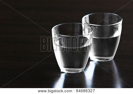 Two glasses of water on wooden background