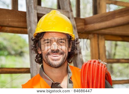 Portrait of happy male worker with pipe in wooden cabin at construction site