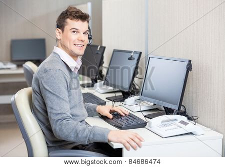 Portrait of young male customer service representative working in office