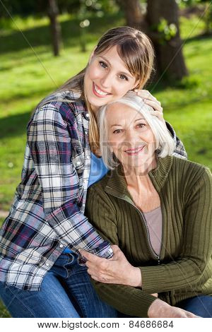 Portrait of smiling young woman embracing mother at campsite