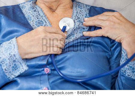 Midsection of senior woman examining herself with stethoscope at nursing home