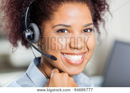Closeup portrait of happy female customer service representative wearing headset in office