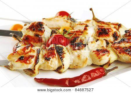 fresh roast chicken shish kebab on white platter