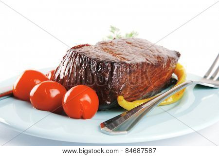 served meat block on blue dish with tomato