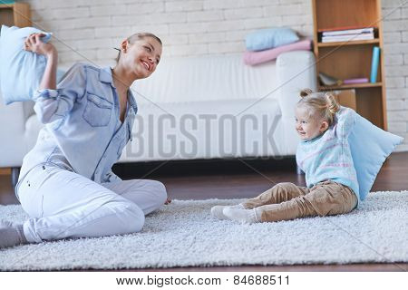 Pretty babysitter playing with little girl