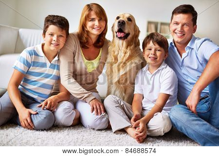 Happy young parents, their children and pet