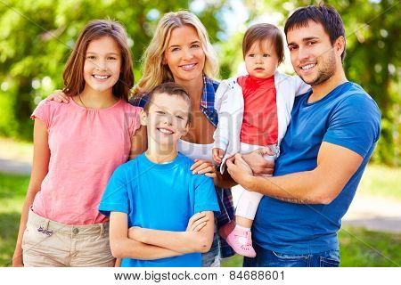 Happy parents and children in casualwear spending leisure outside