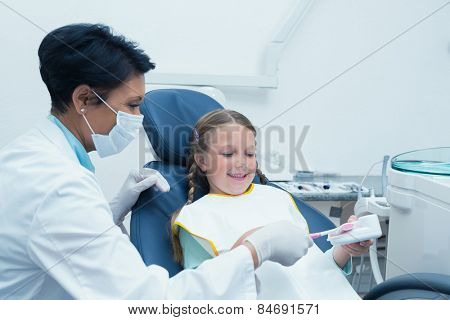 Female dentist teaching girl how to brush teeth in the dentists chair