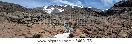 Mount Ruapehu landscape and small watefall flowing under a snow cap in Tongariro National park