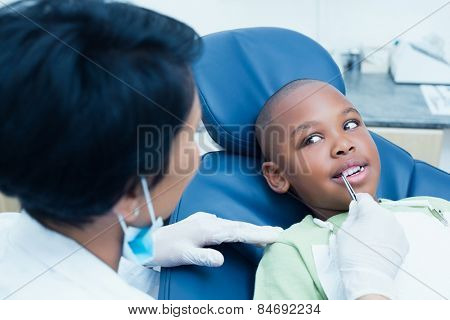 Close up of dentist examining a boys teeth in the dentists chair