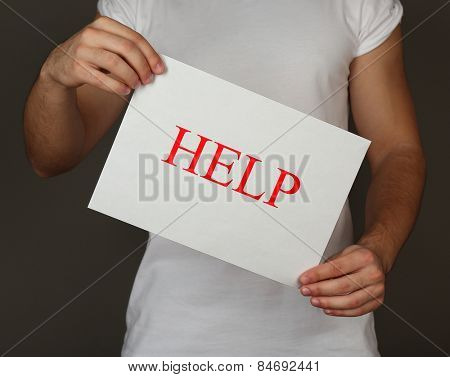 Sheet of paper with Help sign in male hands on dark background