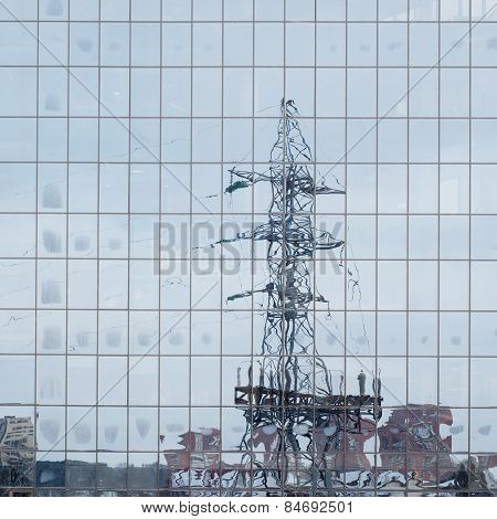 electric pole reflected in windows of office building