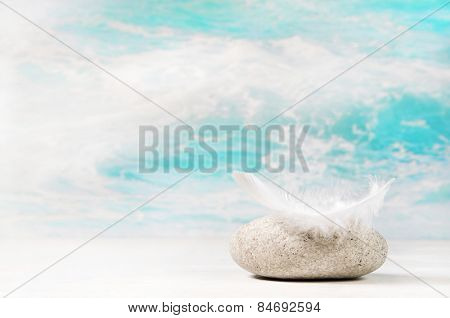 White feather on a stone: background for a condolence or spa concept.