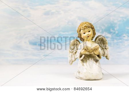 Christmas angel reading in a book telling a story on a background for a greeting card.