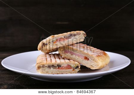 Fresh and tasty sandwiches on plate on wooden background