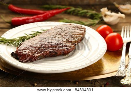 Composition with tasty roasted meat on plate, tomatoes and rosemary sprigs on wooden background