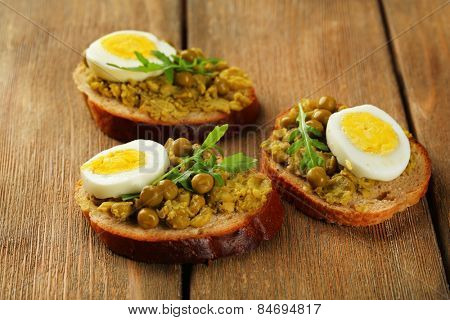 Sandwiches with green peas paste and boiled egg on wooden planks background
