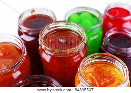 Homemade jars of fruits jam on color table background