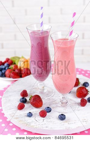 Delicious berry cocktails on table on brick wall background