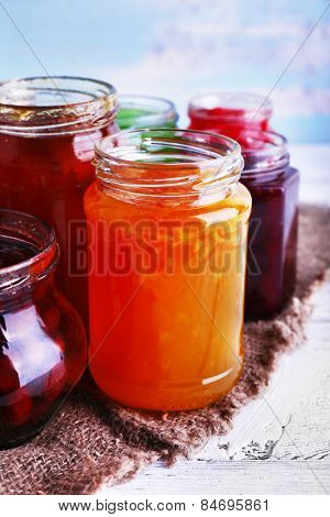 Homemade jars of fruits jam on burlap cloth on wooden table and color wall background