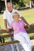 foto of sitting a bench  - Happy senior man and woman couple sitting together outside in sunshine on a park bench - JPG