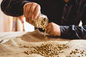 stock photo of minerals  - Young male miner sitting at table and pouring gold out of glass jar  - JPG