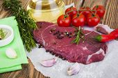 stock photo of beef shank  - Fresh beef steak on plate with aromatic spices on a wooden background - JPG
