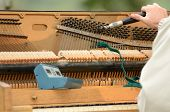 pic of tuning fork  - A piano tuner working on an old upright just before a fair concert - JPG