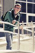 image of school building  - Teen boy with backpack against a school building - JPG