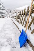stock photo of snow shovel  - A blue snow shovel placed against a fence showing the path that was just cleared - JPG