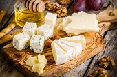 stock photo of brie cheese  - Mix Cheese: Emmental Camembert Parmesan blue cheese with walnuts and honey on wooden table