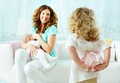 picture of breastfeeding  - Little girl holding a surprise for her mother behind back - JPG