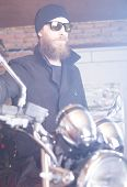 image of chopper  - Bearded man posing with his shiny stylish chopper - JPG