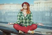 stock photo of redhead  - Hipster redhead woman in hat and glasses doing yoga on the bench in the city - JPG
