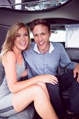 stock photo of limousine  - Happy couple smiling in limousine on a night out - JPG