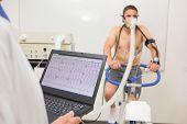 image of exercise bike  - Man doing fitness test on exercise bike at the medical centre - JPG