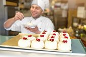 pic of confectioners  - Cakes with confectioner in uniform on the background in the store