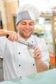foto of confectioners  - Confectioner putting ice cream to the cup for takeaway in the store - JPG