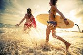 image of friendship  - Two young ladies surfers running into sea with surf boards - JPG