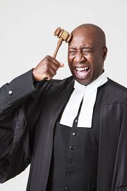 stock photo of toga  - african american bald men wearing a lawyer toga and hitting his head with a gavel - JPG