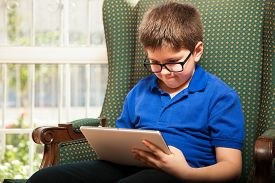 foto of tween  - Cute tween wearing glasses and playing video games on a tablet computer at home - JPG