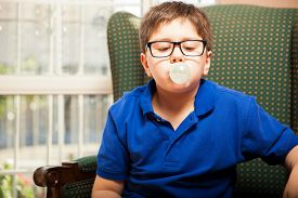 stock photo of tween  - Blond tween with glasses blowing a bubble with some chewing gum at home - JPG